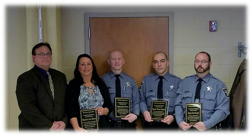 Chief Deputy, Dispatcher and officers holding plaques